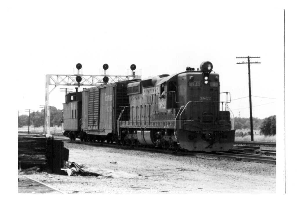 Southern Pacific engine 3822 with one box car and a caboose.