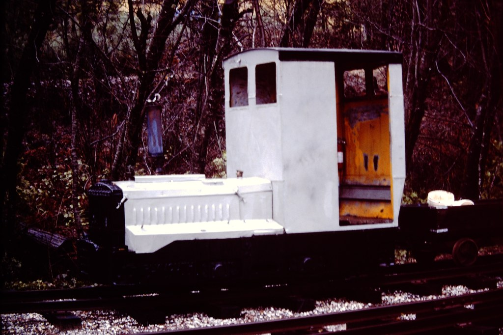 photo of a white home made rail gasoline powered small vehicle with a trailer