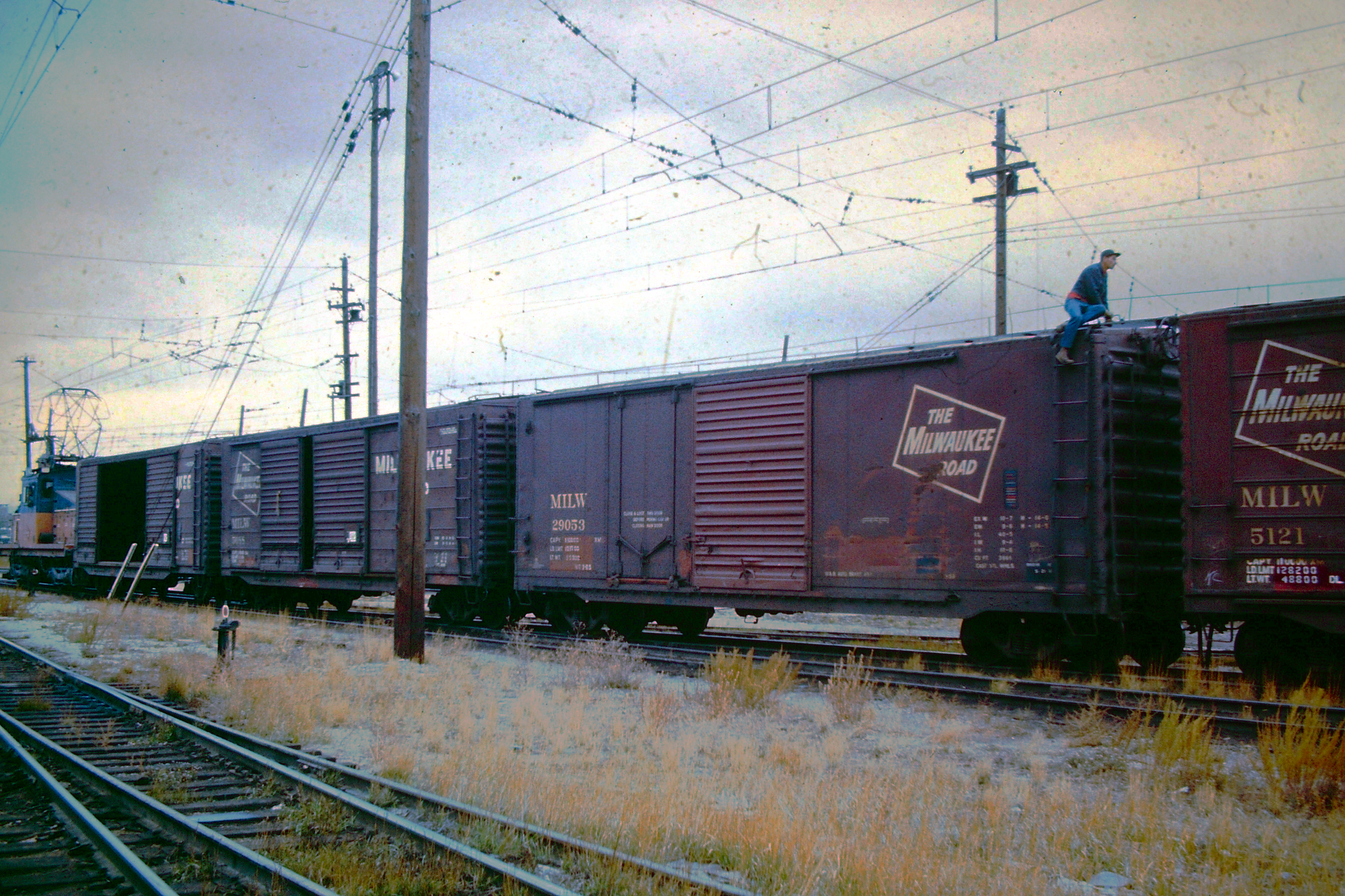 Electric train with boxcars and man on top of one working.
